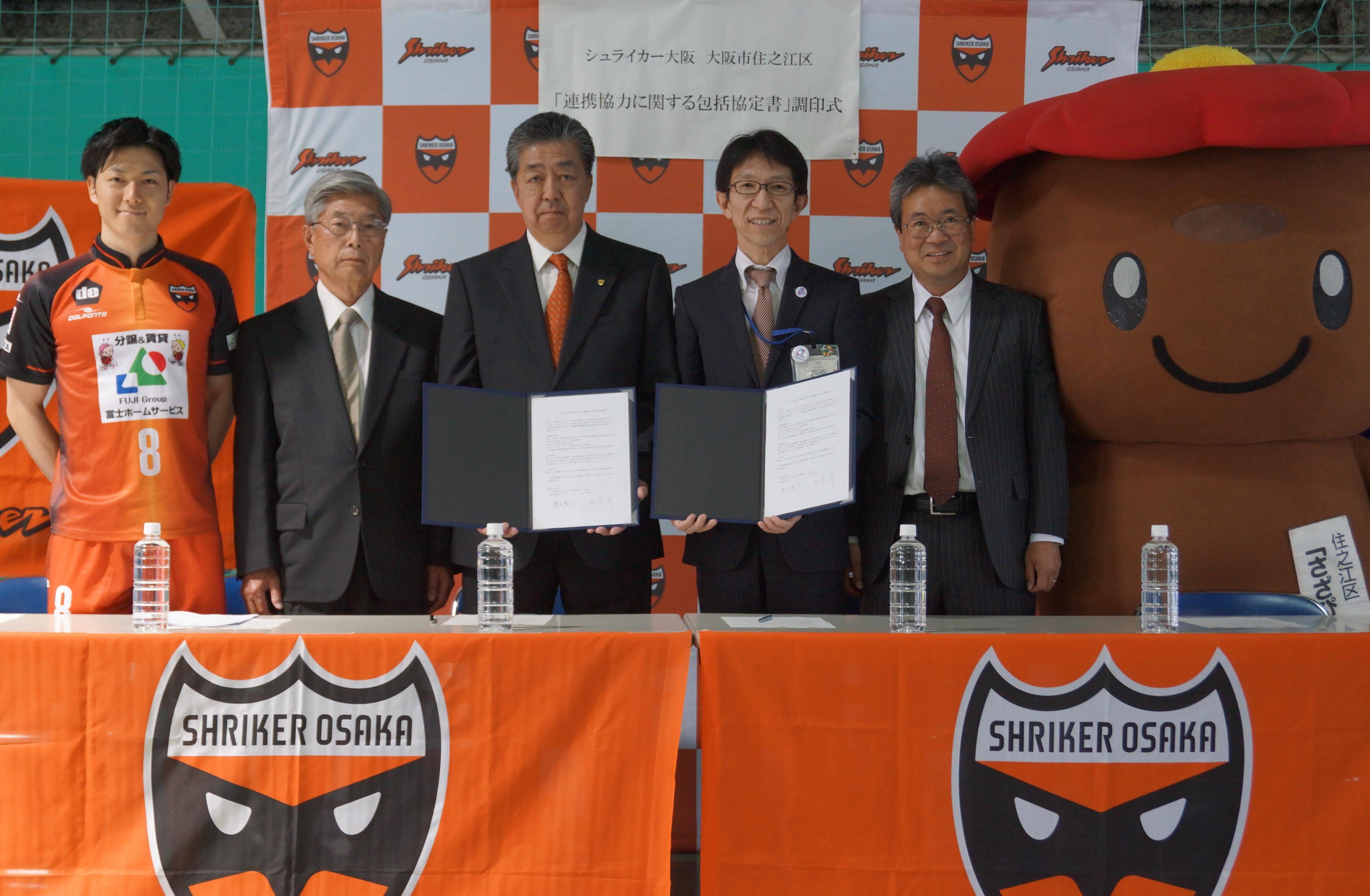 左から加藤選手、山田常務、濵田社長、西原区長、安藤副区長、さざぴーの集合写真