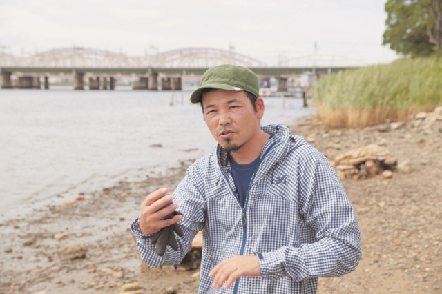 淀川河川敷でごみアートについて語る松永さん 河川敷に突如現れた巨大な魚影。色鮮やかで芸術的なその